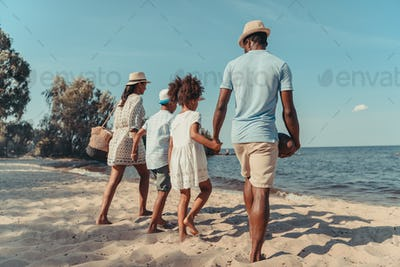 back view of african american family holding hands and walking on beach