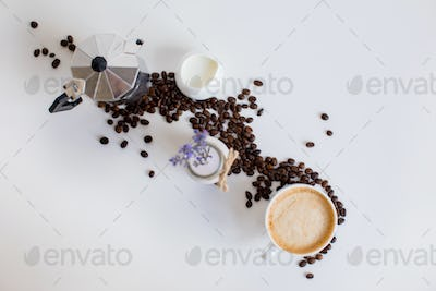 top view of french press, cup of coffee, milk jar and lavender drink with scattered coffee beans,