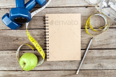 top view of notebook, fresh apple, measuring tape and sport equipment on wooden table