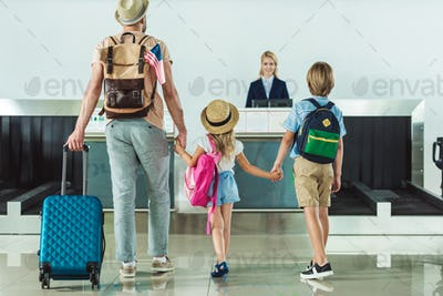 back view of family with backpacks going to check in desk at airport