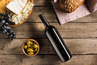 top view of bottle of red wine, green olives, different cheese and bread on napkin on wooden
