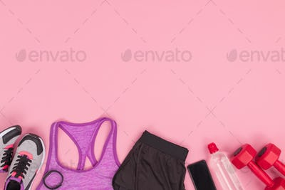 Top view of sportswear with sneakers and fitness equipment isolated on pink