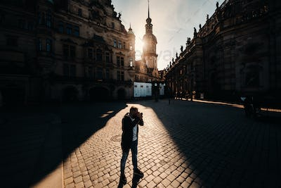 Dresden, Germany a male tourist with a SLR camera travels through Germany.A man photographs the old