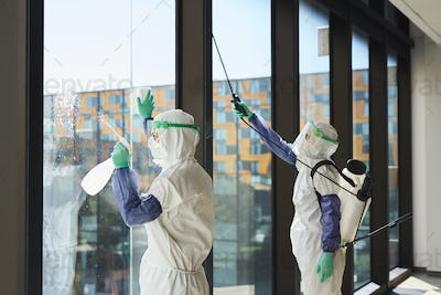 Cleaning Workers Disinfecting Windows in Office