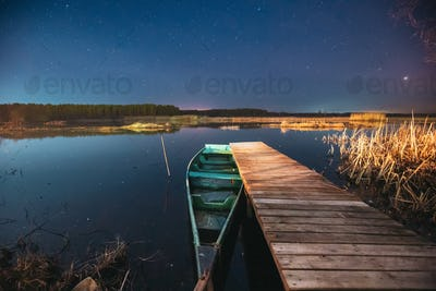 Belarus, Eastern Europe. Real Night Sky Stars Above Old Pier With Moored Wooden Fishing Boat