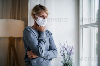 Woman indoors at home feeling stressed, mental health and coronavirus concept