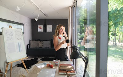 Mature woman working indoors in home office in container house in backyard