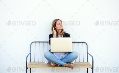 Mature woman working in home office outdoors on bench, using laptop