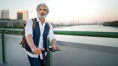 Mature man commuter with electric scooter outdoors in city, going to work. Copy space