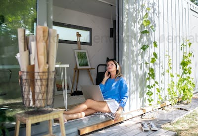 Mature woman working in home office in container house in backyard