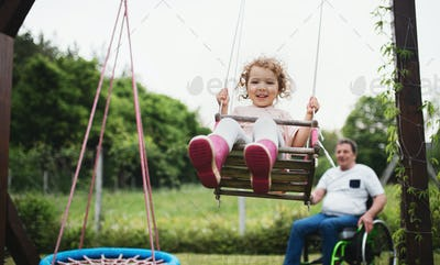Small girl with senior grandfather in wheelchair playing in backyard garden, swinging