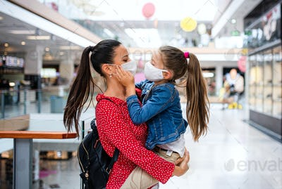 Mother and daughter with face mask standing indoors in shopping center, coronavirus concept