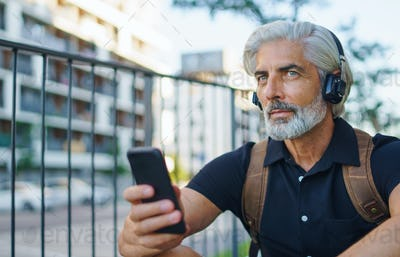 Portrait of mature man with headphones sitting outdoors in city, using smartphone