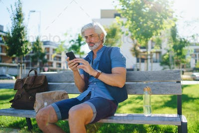 Portrait of mature man sitting outdoors on bench in city, using smartphone