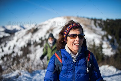Senior woman with husband hiking in snow-covered winter nature