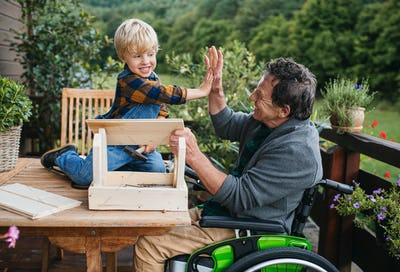 Small boy with senior grandfather in wheelchair constructing birdhouse, diy project