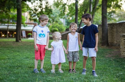 Three young boys and toddler girl in summer park