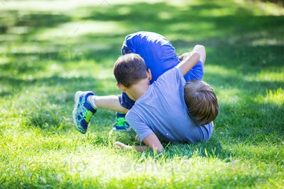 Two boys fighting outdoors. Siblings or friends wrestling on grass in summer park.