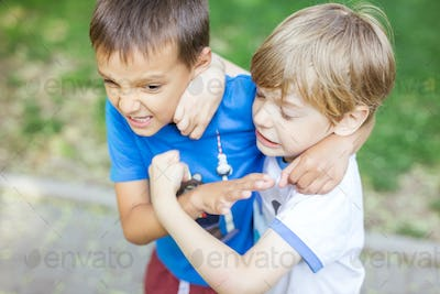 Two boys fighting outdoors. Friends wrestling in summer park.