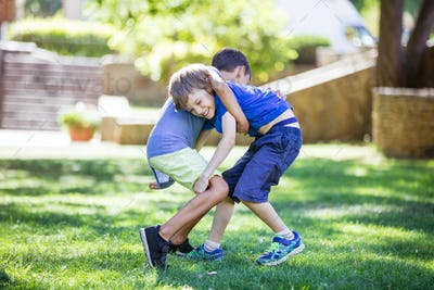 Two boys fighting outdoors. Siblings or friends wrestling in park.