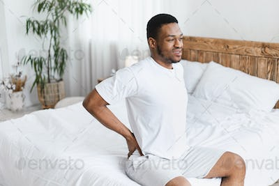 African American Man Touching Aching Back Sitting In Bed Indoors