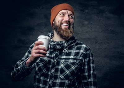 A brutal bearded male dressed in a hat and fleece shirt, drinks coffee from a paper glass.
