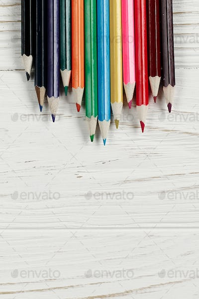 colorful pencils on white rustic wooden background