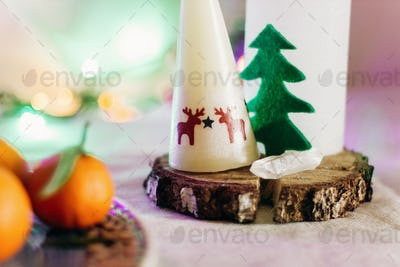candle with reindeers and christmas tree on rustic christmas table with colorful lights