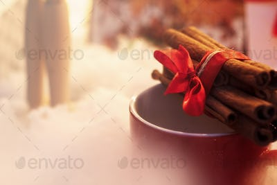 cinnamon sticks with ribbon on red cup