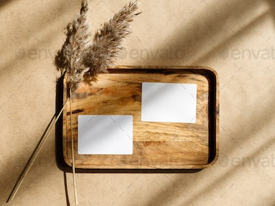 Mockup for business template. Top view of two blank paper sheet cards on a wooden tray