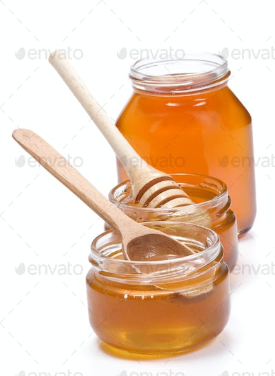glass pot full of honey isolated on white