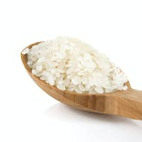rice in wooden spoon isolated on white