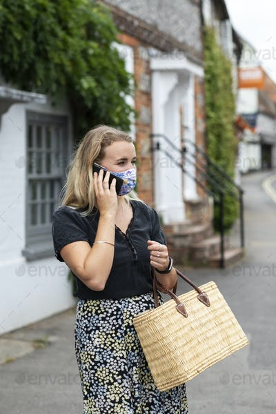 Portrait of young blond woman wearing blue face mask, using mobile phone.