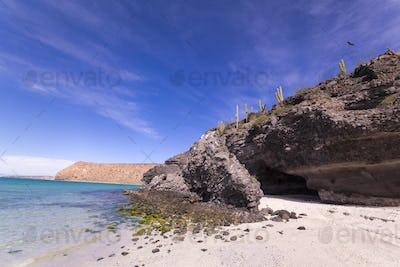 Sandy beach and rocky cliff, Isla Espiritu, Mexico.