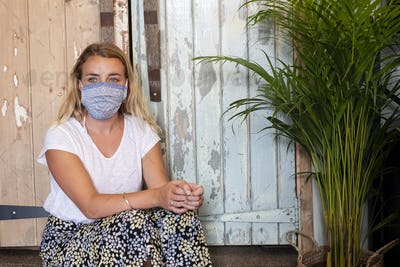 Portrait of young blond woman wearing face mask, sitting in waste free wholefood store.