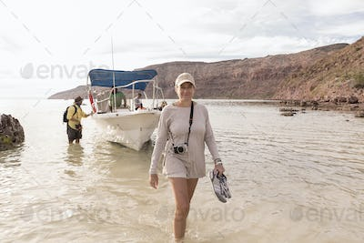 Woman walking to shore from power boat, Sea of Cortes