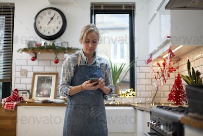 Blond woman wearing blue apron standing in kitchen, using mobile phone.