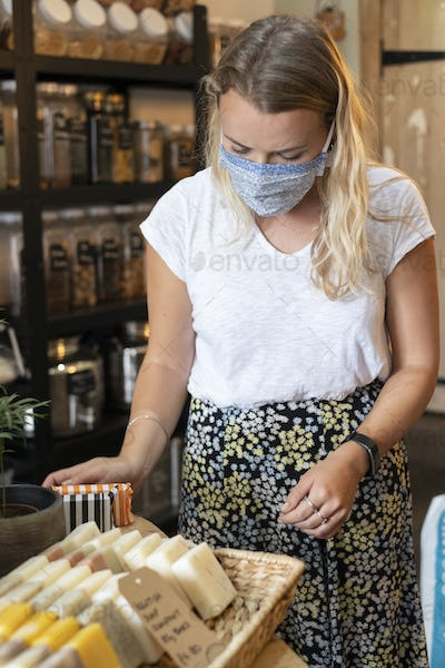 Woman wearing face mask shopping in waste-free local store, sustainability.