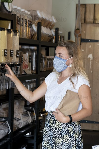 Woman wearing face mask shopping filling a paper bag with loose ingredients