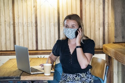 Young blond woman wearing blue face mask, sitting at table, using mobile phone and laptop computer.