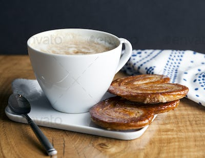 Close up of palmier cookies and cup of coffee