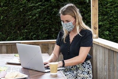 Young blond woman wearing blue face mask, sitting at table, using laptop computer.