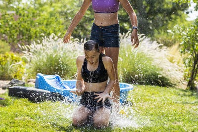 Two teenage girls wearing swimwear playing with water balloons in a garden.