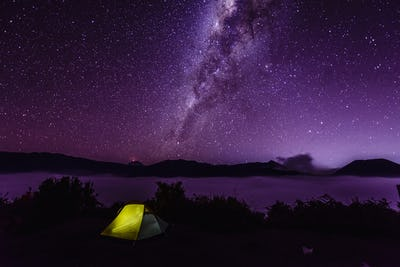 Milky Way galaxy over campsite in starry night sky