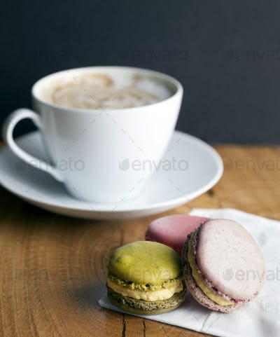 Close up of macaroon cookies and cup of coffee