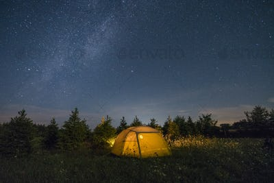 Illuminated camping tent under starry sky