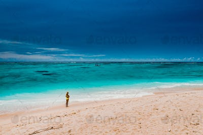 Mauritius, Indian Ocean - portrait of a girl walking along the beach with tourists from all over the