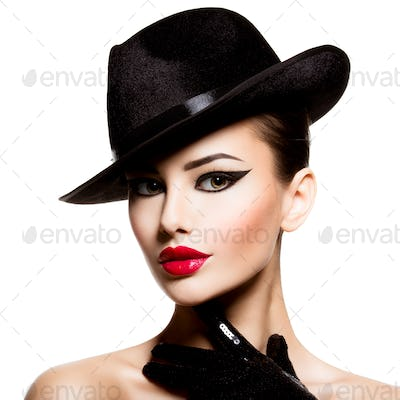 Сlose-up portrait of a woman in a black hat and gloves with red lips