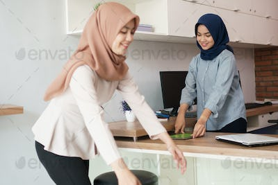 portrait of beautiful muslim woman preparing her office with her partner