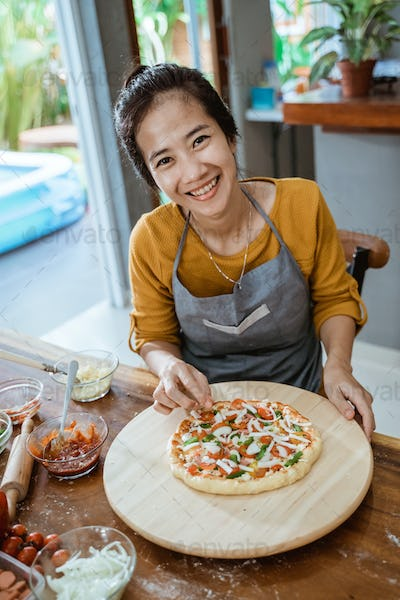 oung woman's hands make a pizza at home